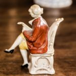 Antique knick-knackery figure, sitting on chairs